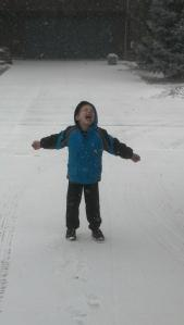 My son delighting in the snowfall